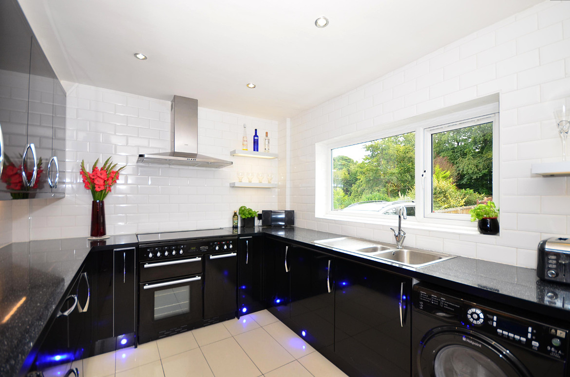 The contrasting black and white colours in this kitchen are brought out by the floor level blue LEDs